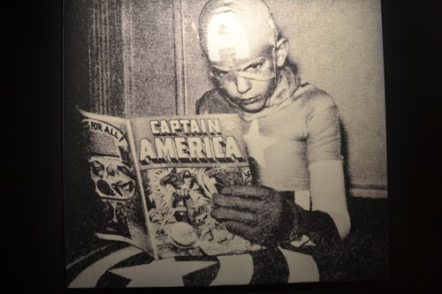 Kid dressed as Captain America reading comics